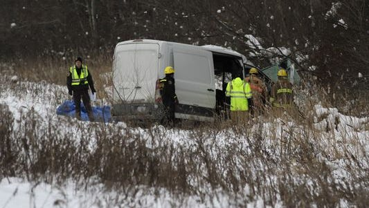 Police inspect a vehicle involved in a serious crash on eastbound I-96 near M-52 on Friday, Dec. 16. The eastbound lanes of the freeway are closed at M-52.