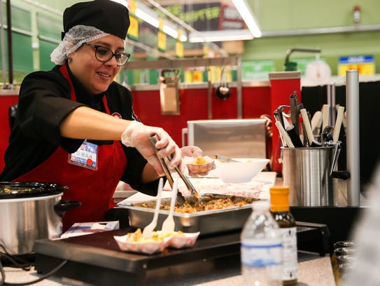 Sheila Flecha scoops out samples during a store tour at San Angelo's H-E-B #2 on Oct. 19, a day before the store opened.