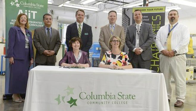 Columbia State Community College and Fairview High School enter into a new Advanced Integrated Industrial Technology program partnership. (seated left to right) Dr. Janet F. Smith, Columbia State president and Dr. Juli Oyer, Fairview High School principal. (Standing left to right) Dr. Margaret D. Smith, Columbia State executive vice president-provost; Mehran Mostaijir, Columbia State AiiT program director; Dr. Dearl Lampley, Columbia State dean of science, technology and mathematics division; Dr. David Allen, WCS career and technical education coordinator; Dr. Charles Farmer, WCS assistant superintendent of secondary schools; and Kevin Sizemore, Fairview High School mechatronics instructor.