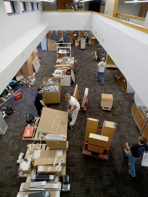New furniture is unboxed and assembled Tuesday afternoon in the main lobby area of the Ashland Public Library.