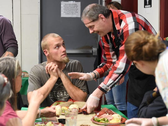A volunteer serves Nathan Davis a meal at the Fort Collins Rescue Mission's annual Christmas banquet on Dec. 22, 2015. Davis wouldn't accept his plate until 'all the ladies' were served.