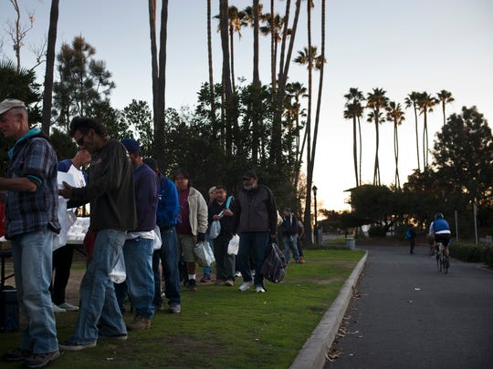 Homeless people wait in line for a free meal Thursday, Dec. 21, 2017, in Dana Point, Calif.
