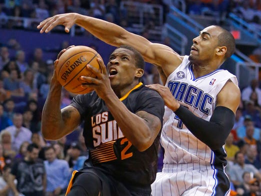 Suns guard Eric Bledsoe (2) is fouled by Orlando Magic guard Arron Afflalo (4) during the first half of their NBA game March 19, 2014 in Phoenix.