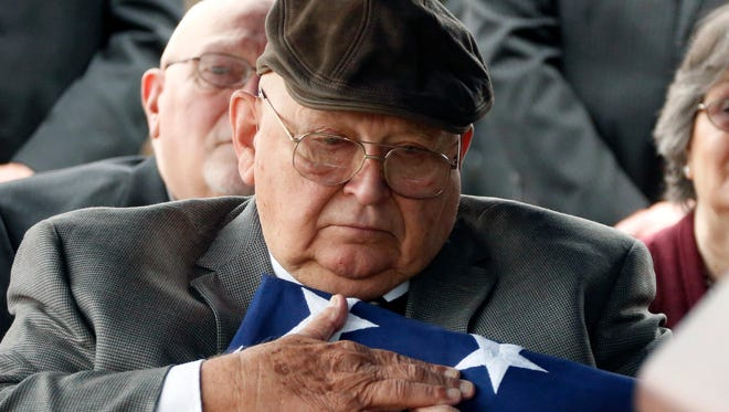 Frank Springs, of Lucedale, hugs the American flag that draped the casket of his uncle, Navy Fireman 1st Class Jim H. Johnston, who was buried Wednesday, Dec. 7, 2016, with full military honors in Wesson, Miss., his hometown. Johnston was one of 429 crewmen killed on the USS Oklahoma when it was attacked by Japanese aircraft on Dec. 7, 1941. The USS Oklahoma capsized quickly after sustaining damage from several torpedoes. Most of the dead were never identified.