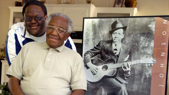 In this Feb. 1, 2006, file photo taken in Crystal Springs, Claud Johnson, seated, son of legendary Mississippi blues artist Robert Johnson, shown in the poster on the right, has died at age 83.
