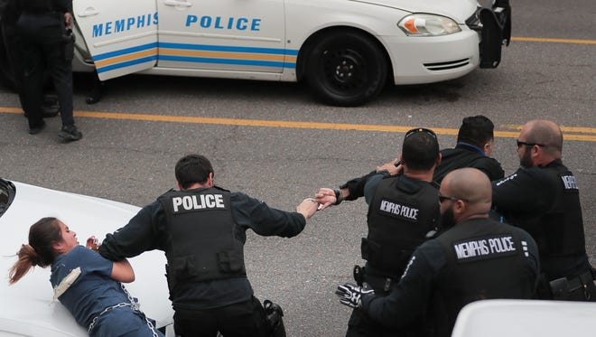 Protesters with Coalition For Concerned Citizens of Memphis, Comunidades Unidas en Una Voz and Fight for 15 clash with Memphis Police outside the Shelby County Justice Center during a demonstration to call attention to immigration issues  Tuesday, April 3, 2018, in Memphis, Tenn. At least eight demonstrators were arrested during the protest.