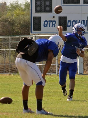Two Desert Christian High School players do throwing drills to improve their accuracy during a practice session at the Conquerors' practice field on Aug. 14, 2015.
