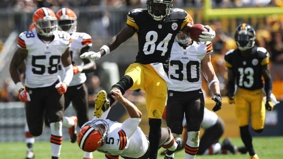 Steelers wide receiver Antonio Brown (84) runs over Browns punter Spencer Lanning during the first half at Heinz Field.