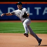 New York Yankees second baseman Dustin Ackley throws to first but New York Mets' Daniel Murphy is able to beat out the throw during the fourth inning of a baseball game, Saturday, Sept. 19, 2015, in New York. (AP Photo/Julio Cortez)