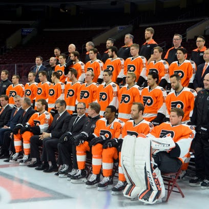General manager Ron Hextall,  front, center, has more