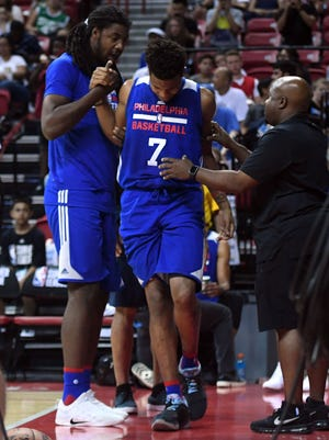 Philadelphia 76ers guard Markelle Fultz is helped off the court after an injury during the second half against the Golden State Warriors at Thomas & Mack Arena.