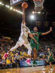 Michigan guard Muhammad-Ali Abdur-Rahkman (12) goes to the basket while defended by Jacksonville guard JD Notae (1) in the second half of U-M's 76-51 win on Saturday, Dec. 30, 2017, at Crisler Center.