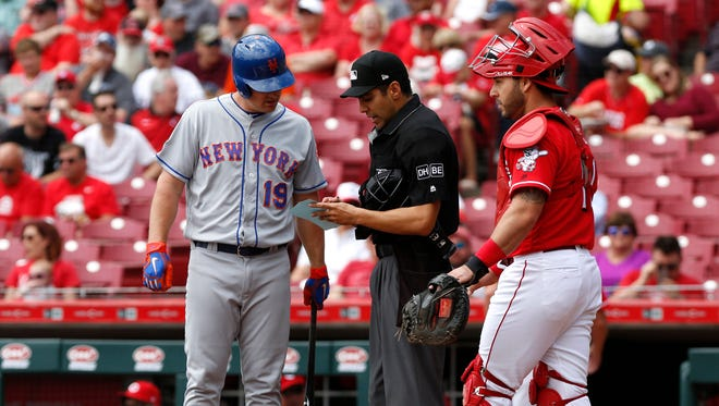 Mets right fielder Jay Bruce looks over the lineup card with home plate umpire Gabe Morales.