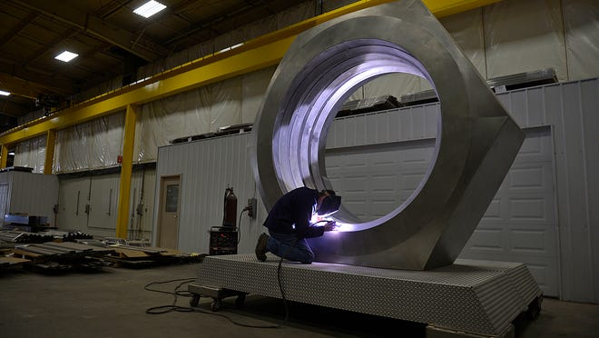 Nick Wegner, a fabricator with Robinson Metal in De Pere, welds the threads to a 10-foot hex nut.