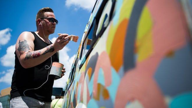 Artist Van Holmgren paints a van during the Des Moines Art Festival in Western Gateway Park on Saturday, June 27, 2015.