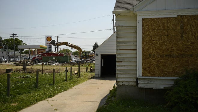 Crews work on demolishing a former gas station and several abandoned homes last week at the intersection of Mason and Bellevue streets on the east side.