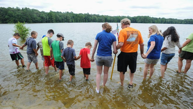 Lisa Baird (center, in white shoes), with the Nanticoke Watershed Alliance, leads a wade-in at Trap Pond State Park, near Laurel.