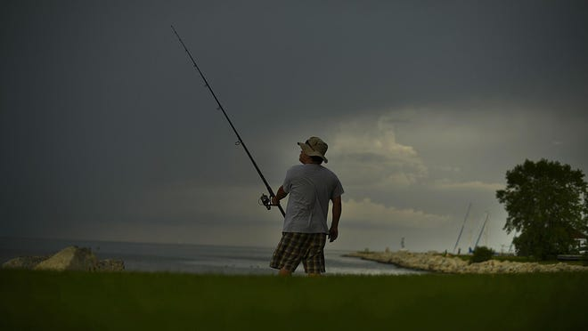 Storm clouds move in Aug. 14 as Larry Tuazon of Brookfield tries his luck fishing along Green Bay.