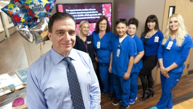 Dr. Benny Benzeevi, left, with staff at Tulare Regional Medical Center on Monday.