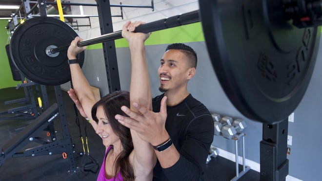 Personal trainer Eddie Renteria works with Connie Chamberlain on lifting at this new fitness facility Elite Results III in Visalia on Wednesday, November 18, 2015.