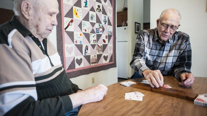 Ted Garnett, left, and Jim Geiger play cribbage in Geiger's Conrad home, as the WWII veterans do every week.