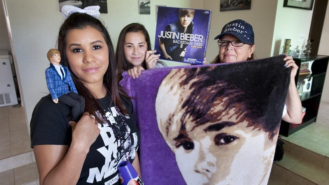 Larissa Mora, 18, left, Marina Lopez, 15, and their grandmother Mary Lou Guerrero, 58, show their interest in Justin Bieber on Wednesday, March 23, 2016. Guerrero and Mora have tickets for his show in Fresno on Saturday.