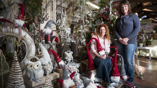 Meghan Kelly, the general manager, and Angie Brown, the greenhouse manager, show off one of several holiday displays at Electric City Conservatory.