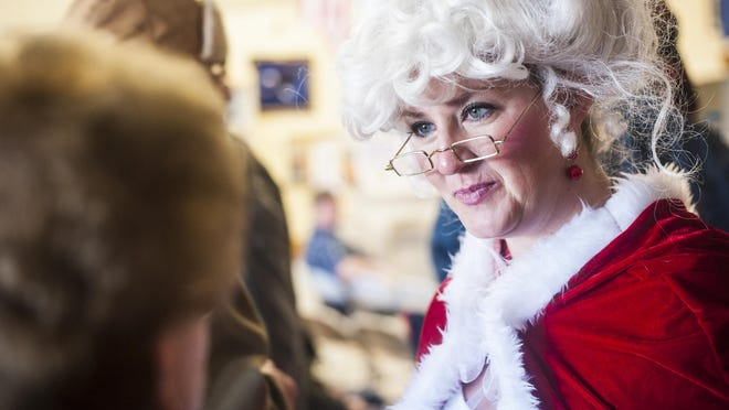 Brianne Sinnott helps seat visitors while dressed as Ms. Claus during the Danny Berg Memorial Dinner.