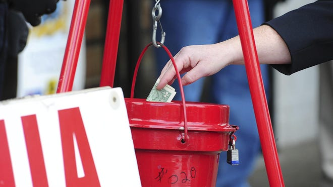 In this Nov. 22, 2017, file photo, a patron donates money in a Salvation Army red kettle in Wilkes-Barre, Pa.