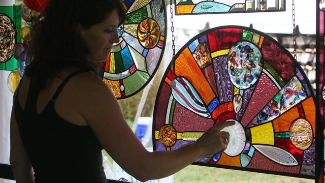 Karri Mohr of Milford, Mich., looks at glass creations in the Ohio Art Glass booth on the grounds of Stan Hywet Hall & Gardens  on Friday, Oct. 4, 2013.