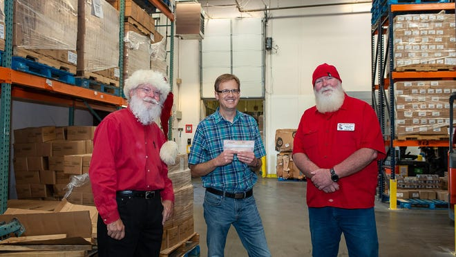 The Lone Star Santas organization makes a $2,500 donation to the local High Plains Food Bank. Raymond Hill ( Santa Ray) and Chrys Griffing (Santa Chrys) present the check to Zack Wilson of the food bank.