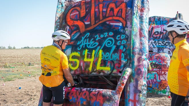 Don Montano paints a S4L (smile for life) on one Cadillac Friday morning at Cadillac Ranch. He is part of the group bicycling across America to help raise funds for the Smile For A Lifetime organization. The group got to help decorate the Cadillacs before riding on into Amarillo.