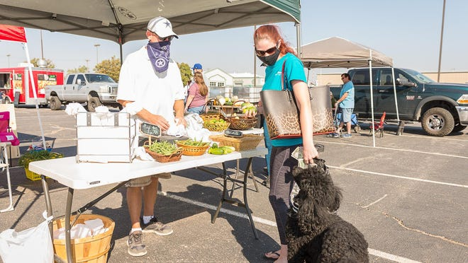Tim Smith sells produce to Megan Ahaf with her dog Rayne during Saturday's Harvest Market, the last Amarillo Community Market of the season.