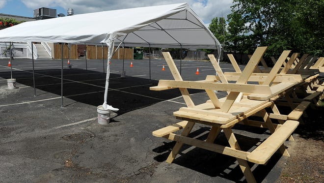 Picnic tables are stacked next to a tent behind the Samba Steak and Sushi Restaurant in Framingham.