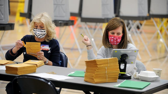 Election workers MaryBeth D'Errico, left, and Diann Ewanchuk open early ballots while early voting continues inside the Franklin High School gymnasium Tuesday morning,