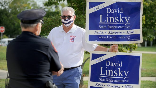 State Rep. David Linsky speaks with Natick police officer John Haswell outside the Natick High School voting place Tuesday.