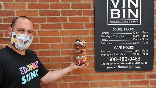 Mike Lombardi, whose parents own the Vin Bin in Marlborough, holds a stack of his specialty doughnuts.