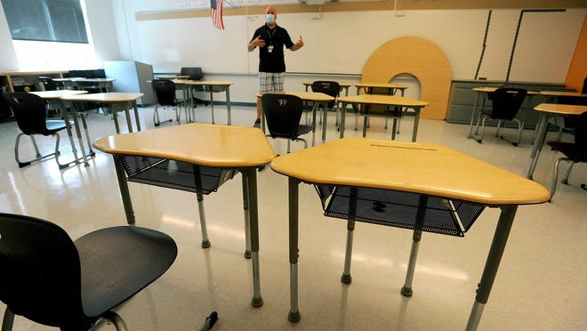 Tim Kearnan, Principal of Woodland Elementary School in Milford, in a classroom. Each double desk setup will have one student seated at any one time.