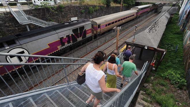 Commuters descend the stairs leading to a commuter rail train in Natick. The MBTA has scheduled 11 virtual meetings in November and early December to solicit commuter input on train, bus and ferry services as it weighs tens or hundreds of millions of dollars in cuts to close a budget deficit fueled by declining ridership.