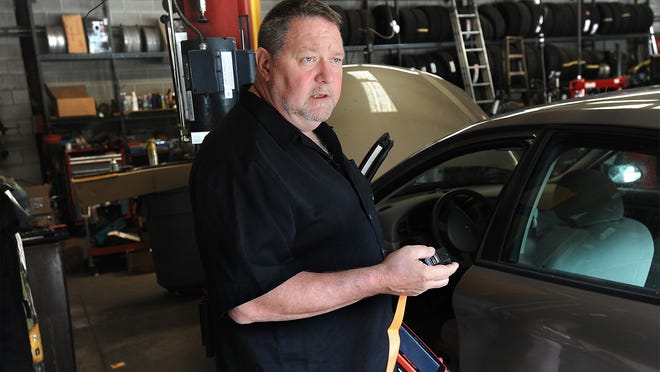 Nice Car Care co-owner Jim Norris holds a computer scanner and a dongle in his Franklin car repair shop last year. The State Ballot Law Commission must now decide whether the Right to Repair question is eligible to reach the ballot.