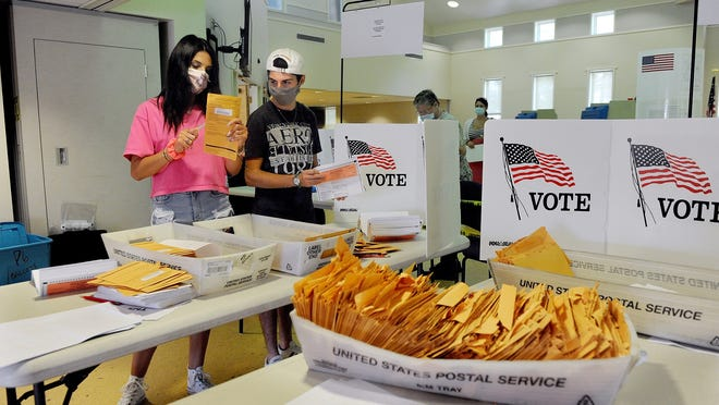 Milford High School seniors and National Honor Society members Ashley Zagame and Eric Doucette open mail-in ballots at the Milford Senior Center voting location Tuesday.