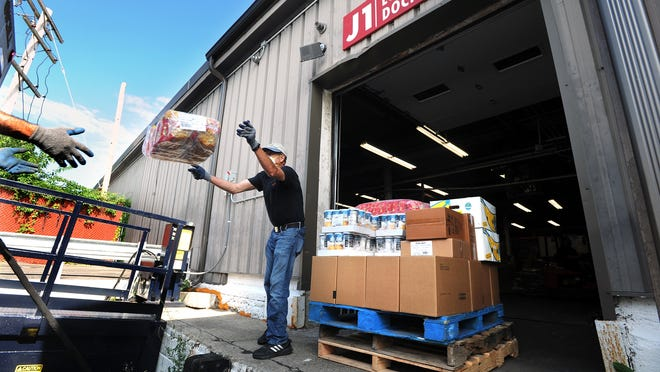 Guillermo Viscarra, a volunteer from the Franklin Food Pantry, throws boxes of food to Andy Keesan, not pictured, at the United Way of Tri Country food warehouse on Blandin Avenue in Framingham on Thursday, July 23.