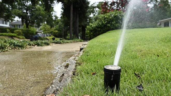 A sprinkler waters the lawn of a Summerville home in Augusta. Too much watering can harm your lawn and plants.