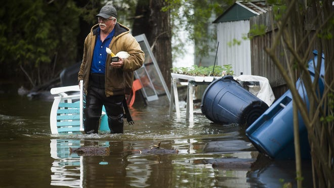 """Mark Musselman brings a chair to the front of his house from the back yard, wading through floodwater, Tuesday, May 19, 2020, in Edenville. An evacuation order was released the night before for residents of Sanford and Wixom Lakes, warning of """"imminent dam failure."""" """"We're all safe, that's the main thing,"""" said Mark's wife, Ruth Musselman."""