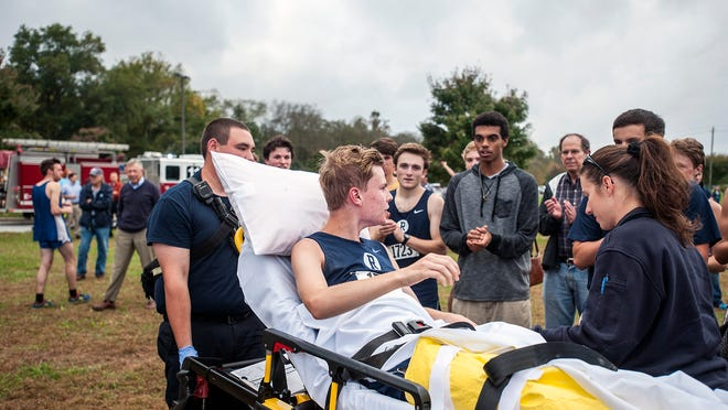 Connor Callihan, Roberson junior cross country runner, waves to his teammates as he's taken to an ambulance with a broken leg. Callihan fell and broke his leg about 10 feet from the finish line Monday during the Mountain Athletic Conference Cross-Country Championships in Fletcher.