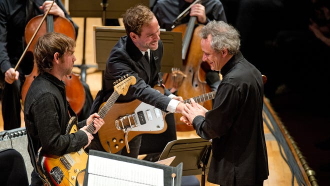 Cincinnati Symphony Orchestra conductor Louis Lang congratulates Bryce Dessner and his brother Aaron Dessner after a performance of Bryce's piece, St. Carolyn by the Sea, during the 2014 MusicNOW festival at Music Hall.