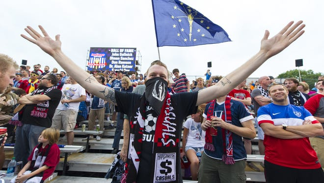 An Indy Eleven fan cheers during pre-game activities in the Brickyard Battalion section. Indy Eleven hosted New York Cosmos in NASL soccer action at Michael A. Carroll Track & Soccer Stadium in Indianapolis, Saturday, August 30, 2014.