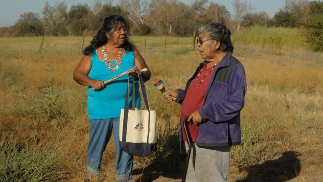 Jennifer Malone, left, and Marie Wilcox, both of the Wukchumni tribe, sing a song Thursday morning and bless 22 acres of land that was recently added to the Kaweah Oaks Preserve.