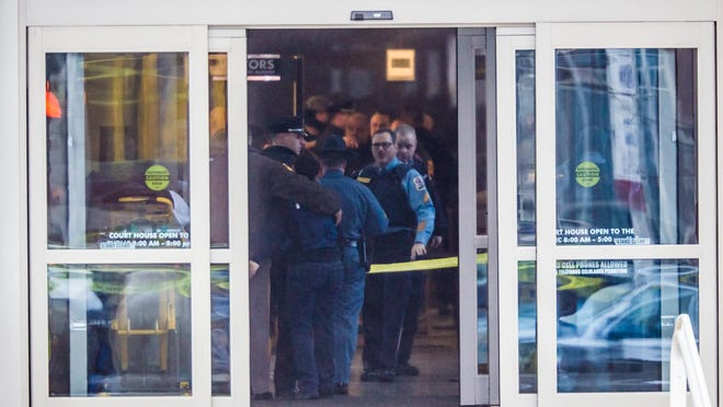 Two officers console each other inside the lobby of the New Castle County Courthouse on Feb. 11, 2013.