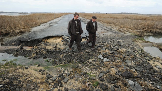 Bart Wilson, of the Prime Hook National Wildlife Refuge, left, and Al Rizzo, of the Coastal Delaware National Wildlife Refuge Complex, walk through a washed-out area on March 26. Fowler Beach for years has had problems with erosion.
